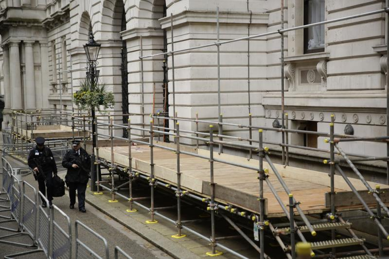 British police officers walk past newly erected media stands for the general election in Downing Street, London, on Tuesday. Britain goes to the polls on Thursday.
