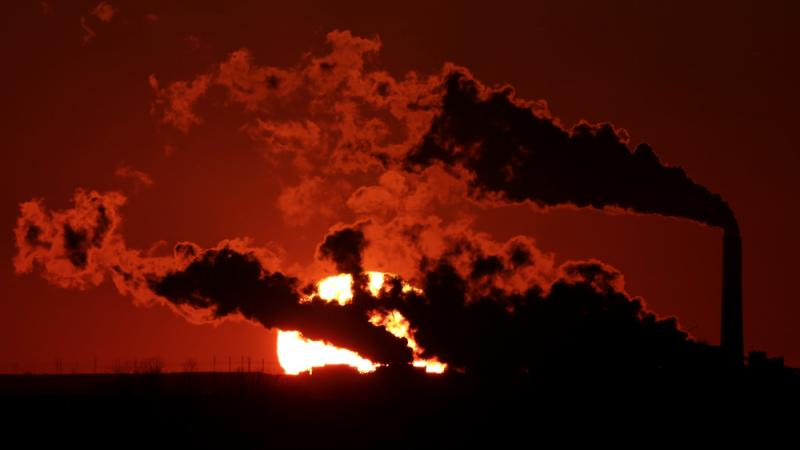 Steam from a coal-fired power plant is silhouetted against the sun near St. Marys, Kan. Industry groups say there should be a far more aggressive consideration of costs of regulation than the Obama administration took into account.