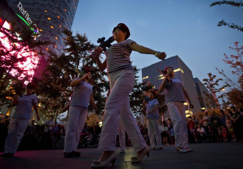 Chinese women holding toy guns dance to a revolutionary song during their daily exercises at a square outside a shopping mall in Beijing. The Chinese government is beginning to regulate public square-dancing, after the practice drew complaints about noise