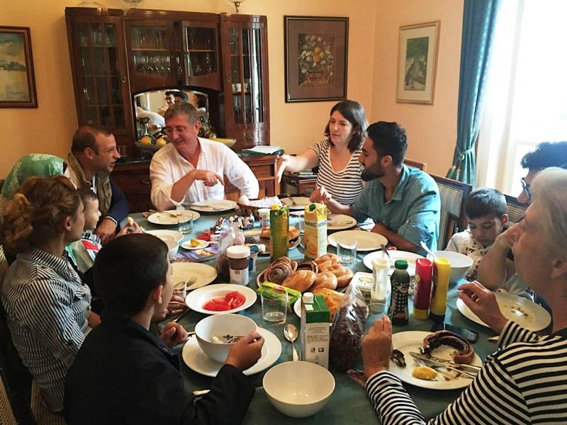 Former Prime Minister Ferenc Gyurcsany and wife Klara Dobrev (at top right) host breakfast for migrants at their home in Budapest.