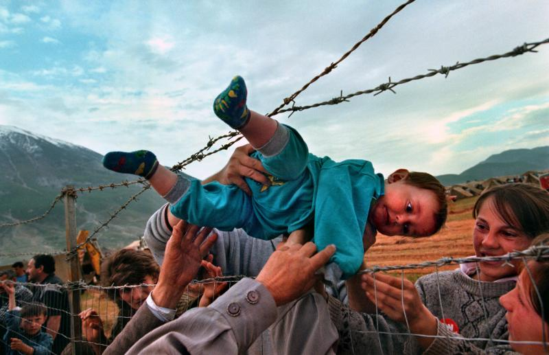 Family members, reunited after fleeing Kosovo, pass 2-year-old Agim Shala through the barbed wire fence into the hands of his grandparents at a camp in Albania. The photo was taken on March 3, 1999.