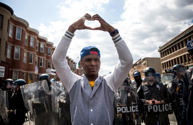 A man makes a heart shape with his hands during a peaceful protest near the CVS pharmacy that was set on fire on Monday in Baltimore.