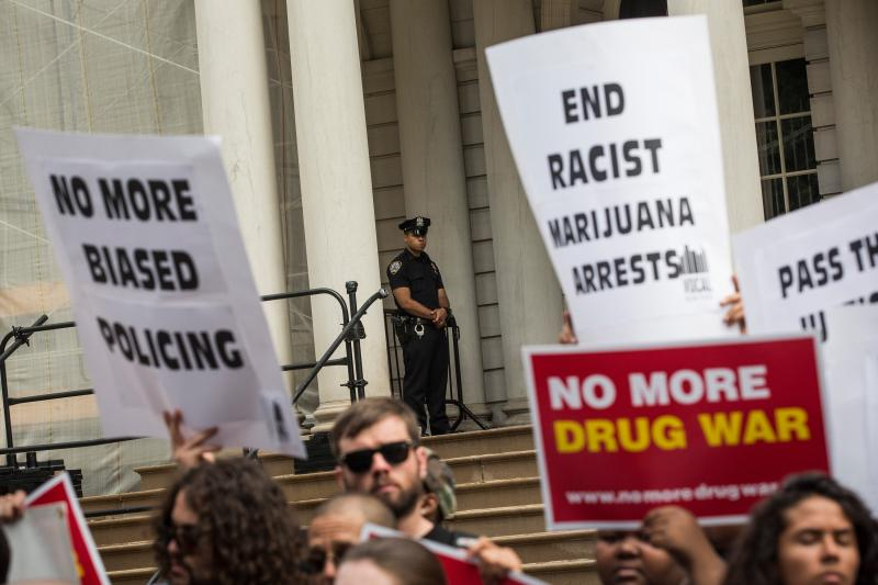 Outside New York City Hall, a policeman watches a protest against racial disparities in marijuana arrests. The majority of those arrested are black or Latino, even though those groups are not more likely to smoke pot.