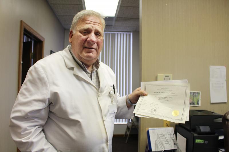 Dr. David Burkons holds the licensing certificates that allowed him to open a clinic that provides medical and surgical abortions. It took about 18 extra months of inspections, he says, to get the approval to offer surgical abortions.