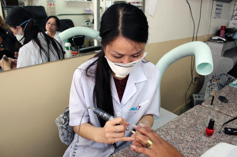 Mai Dang, who owns Fashion Nails in Berkeley, Calif., does a client's nails. The ventilator hose poised over her shoulder helps keeps noxious fumes at bay.
