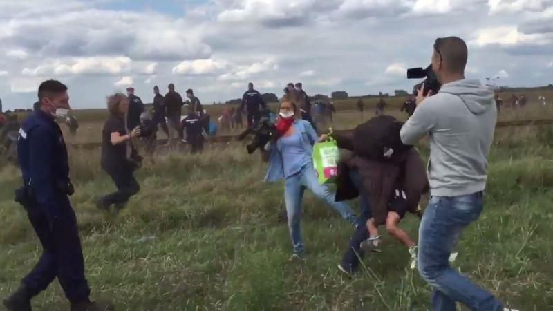 A videographer for a Hungarian TV network trips a migrant holding a young boy who was running away from police. The camerawoman was fired.