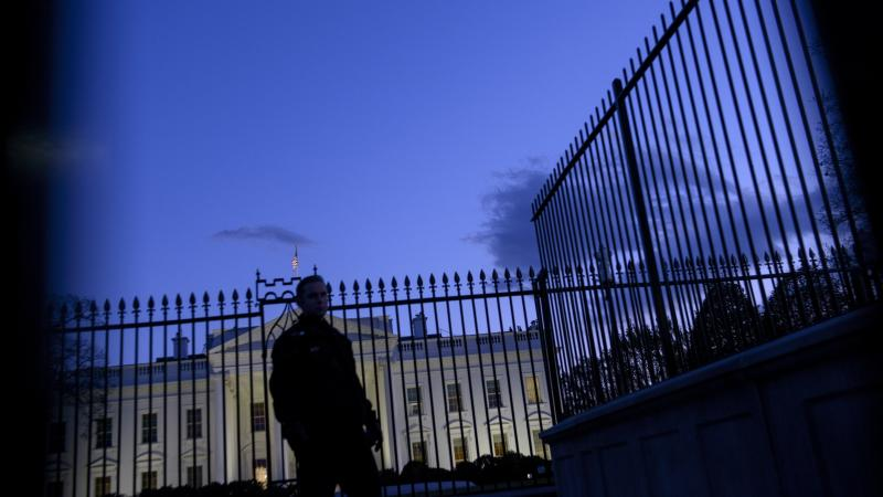 A member of the Secret Service's uniformed division stands by a fence in front of the White House.