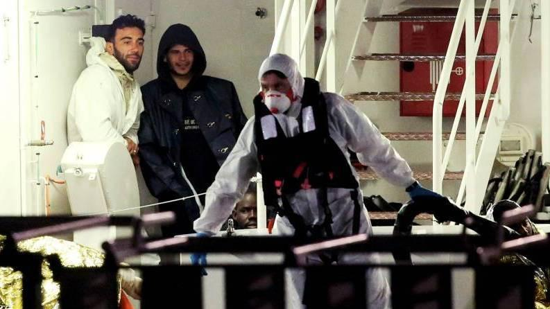 Mohammed Ali Malek (left) and Mahmud Bikhit (center) were identified by survivors as the captain and a crew member of the vessel that sank in the Mediterranean this weekend. They're seen here shortly before an Italian coast guard ship took them to Catania