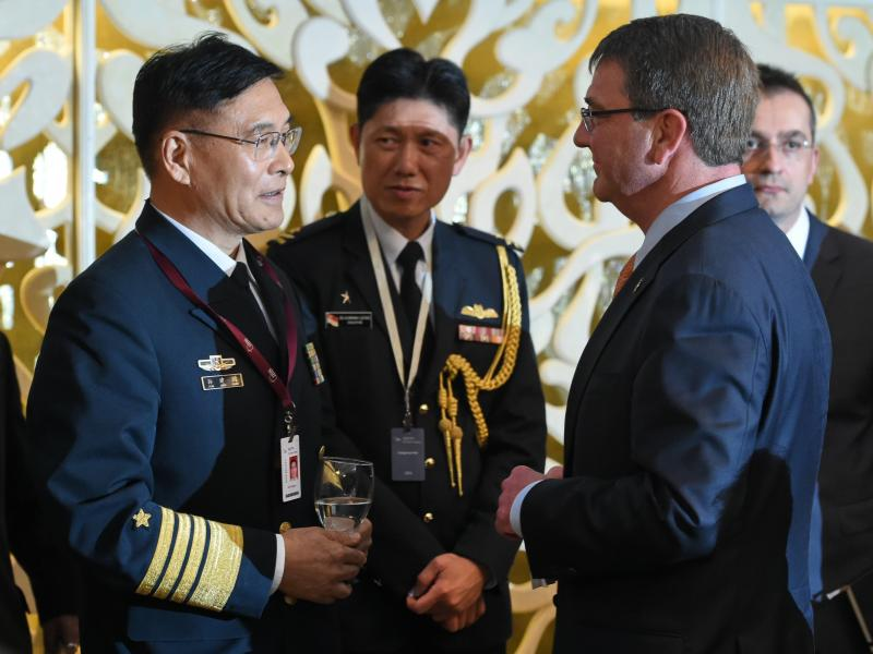 Sun Jianguo (left), from the Chinese People's Liberation Army Navy, chats with U.S. Secretary of Defense Ashton Carter in May during the ministerial luncheon at the 14th Asia Security Summit in Singapore. Each country has grown increasingly wary of the ot