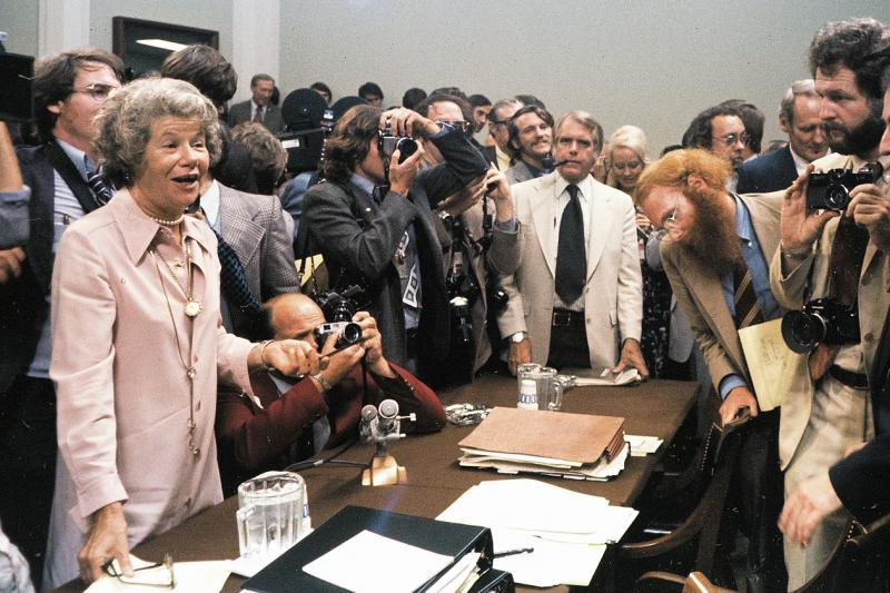 Columnist Mary McGrory holds court among reporters and observers at the 1973 Watergate hearings.