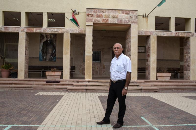 Principal Ali Shalalha stands at the entrance of the high school. Though the school has closed for summer, it's filled with students who are studying for exams.