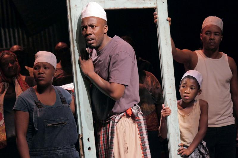 Somali refugee Asad Abdullahi is played by four different actors, each wearing the same white hat: (left to right) Zoleka Mpotsha, Ayanda Tikolo, Siphosethu Juta and Luvo Tamba.