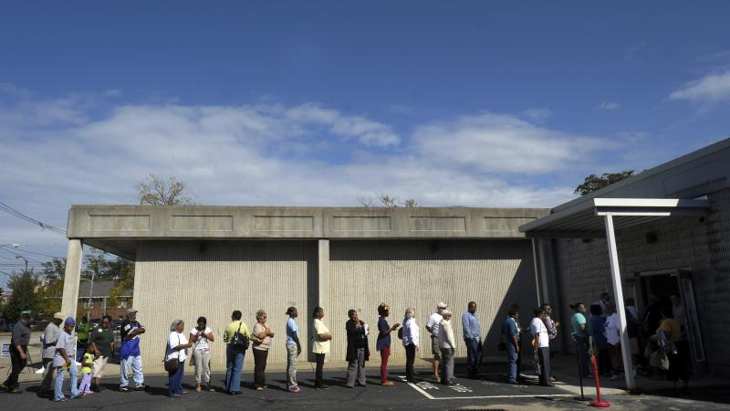 People wait in line to vote at the Board of Elections early voting site on Oct. 18, 2012, in Wilson, N.C. The U.S. Justice Department and several groups are suing North Carolina over the sweeping election overhaul it passed two years ago.