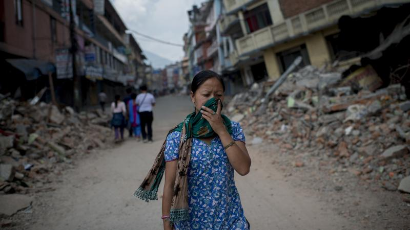 A woman in Kathmandu walks past rubble following several massive earthquakes in Nepal. Officials say at least 76 people died in Tuesday's magnitude-7.3 quake.