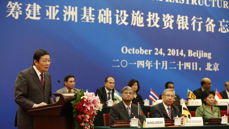 Chinese Finance Minister Lou Jiwei (left) speaks during the signing ceremony of the Asian Infrastructure Investment Bank, Oct. 24, in Beijing.