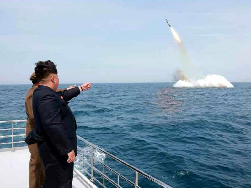 An image obtained by Yonhap News Agency showing North Korean leader Kim Jong Un pointing at a ballistic missile believed to have been launched from underwater near Sinpo, on the northeast coast of North Korea, on Saturday.