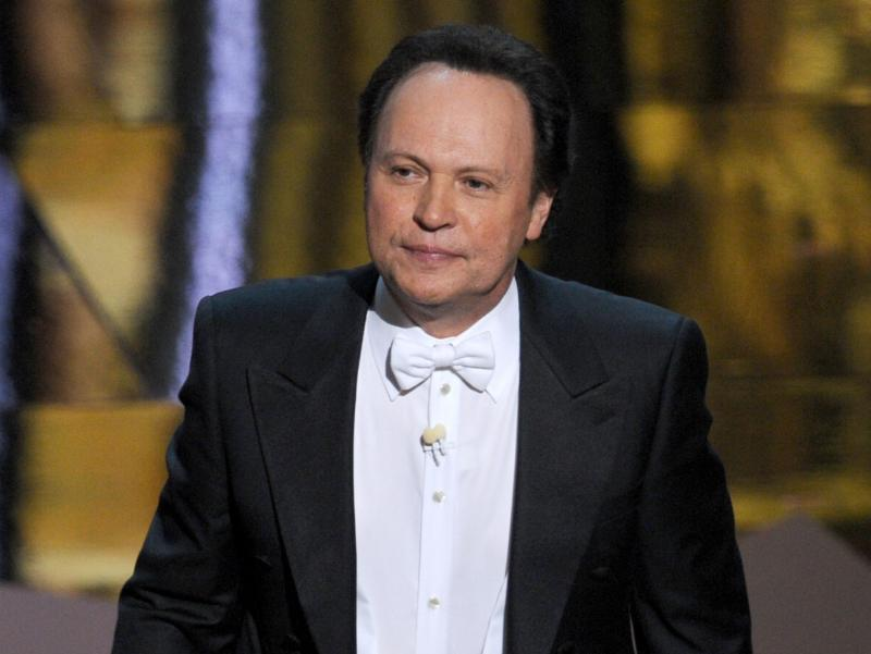 Billy Crystal hosts the 84th Annual Academy Awards in 2012. Writing jokes for hosts is a tricky game, says longtime joke writer Dave Boone.