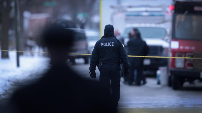 Police investigate the scene of a quadruple homicide in Chicago on Dec. 17.
