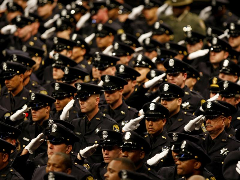 File photo of the Oakland Police Department as they salute at the public memorial service for slain Oakland police officers.
