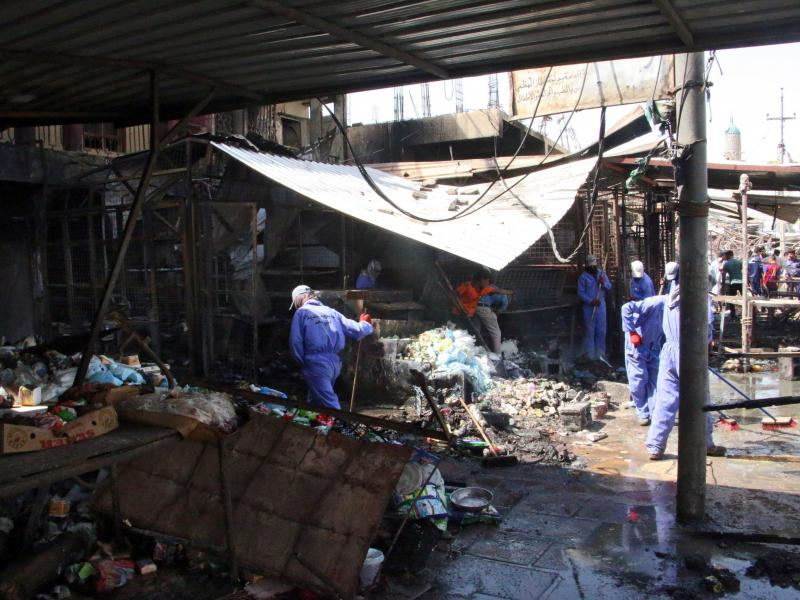 Iraqi workers clean the site of a truck bomb attack that hit the area a day earlier at Khan bani Saad town, eastern Baghdad, Iraq, on Saturday. At least 115 people were killed in what's described as the single deadliest such attack in the country in a dec