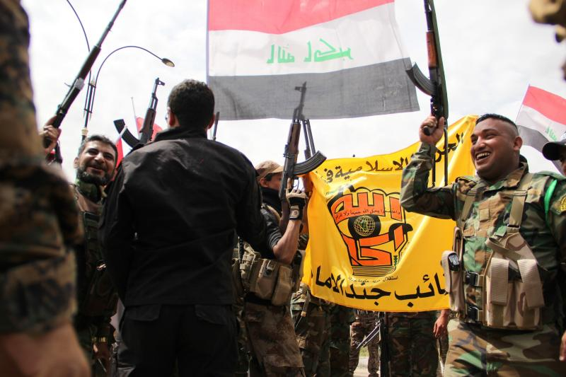 Iraqi forces, including soldiers, police officers and militiamen,  celebrate after retaking the city of Tikrit on Wednesday. Most of the Iraqi forces are Shiite Muslims, while Tikrit's residents are overwhelmingly Sunni Muslims.
