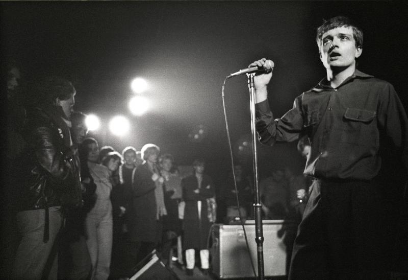 "Singer Ian Curtis on stage in 1980 with Joy Division, whose song ""Transmission"" is among those explored in Greil Marcus' book The History of Rock 'N' Roll in Ten Songs."