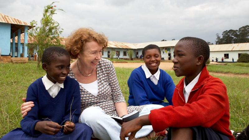 """Ann Cotton, pictured with students in Tanzania, makes sure girls have the funds for everything from books to shoes, so they won't """"feel like a poor relation"""" in school."""