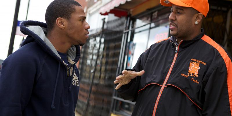 """Ricardo """"Cobe"""" Williams, wearing the cap, served time for attempted murder before joining CeaseFire as a """"violence interrupter."""" Above, he talks with Lil Mikey in a scene from the documentary The Interrupters. Lil Mikey, who'd also been in prison, went on"""