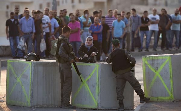 Israeli police check Palestinian IDs at a checkpoint in an Arab neighborhood of Jerusalem on Sunday. Palestinian assailants have carried out a series of stabbings and the Israelis have ramped up security measures in the city. Eight Israelis and more than