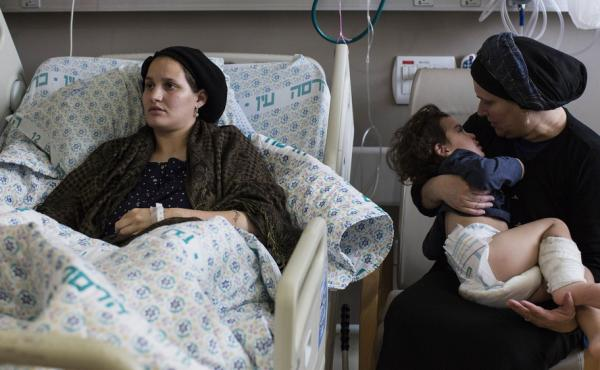 Odel Bennett, a 22-year-old Israeli woman, lies on a hospital bed as her mother Miriam Gal holds Odel's son Natan, 2, at the Hadassah Medical Center in Jerusalem. Bennett was stabbed in an Oct. 3 attack by a Palestinian that killed her husband and lightly