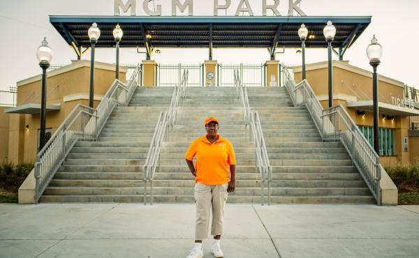 """Qumotria Kennedy, 36, stands at the baseball field in downtown Biloxi where she worked as a contract maintenance employee. She's a plaintiff in an ACLU lawsuit accusing the city of operating an illegal """"debtors' prison."""""""