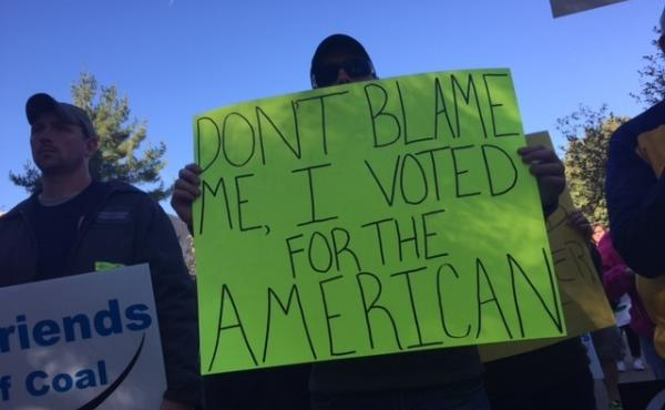 """A protester in West Virginia holds a sign ahead of President Obama's speech on drug abuse that reads, """"Don't blame me. I voted for the American."""""""