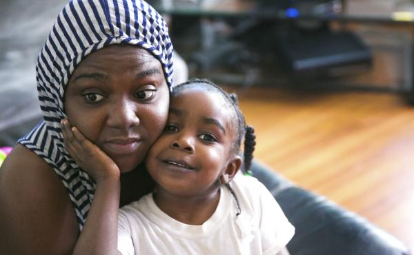 Carmesha Rogers snuggles with her 4-year-old daughter, Kasharee, on Aug. 22, in Muskegon, Mich. Rogers sustained a gunshot wound to the head on July 9 after removing several neighborhood children from a gunbattle's line of fire.  Rogers says her only thou