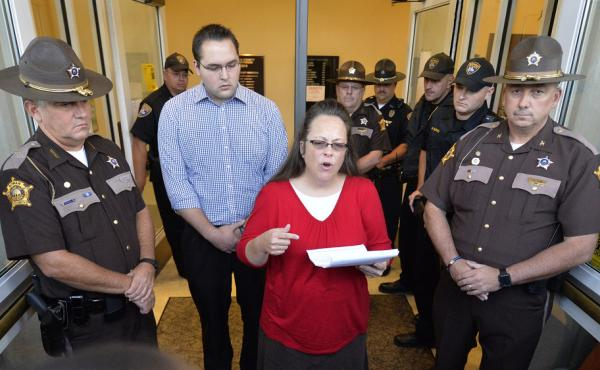 Surrounded by sheriff's deputies, Rowan County Clerk Kim Davis, with her son Nathan Davis standing by her side, makes a statement to the media Monday at the front door of the county Judicial Center in Morehead, Ky.