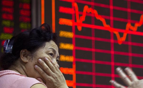 A Chinese investor monitors stock prices at a brokerage in Beijing on Wednesday. The country's stock markets have nosedived.