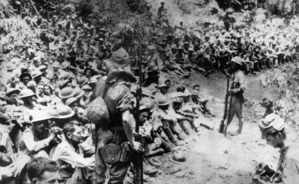 In this 1942 file photo provided by the U.S. Marine Corps, Japanese soldiers stand guard over American prisoners of war just before the start of the Bataan Death March following the Japanese occupation of the Philippines. Some of those who survived the de
