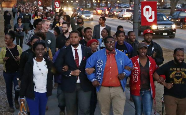 University of Oklahoma students march to the now-closed Sigma Alpha Epsilon fraternity house during a rally against racism Tuesday. Two former members of the fraternity have apologized for their roles in a video that showed them singing a racist chant.