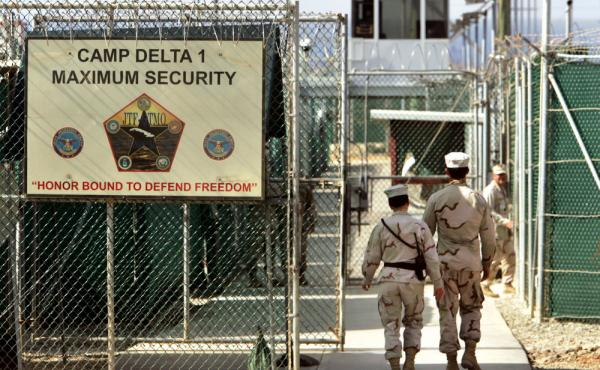 In this June 27, 2006, file photo U.S. military guards walk within Camp Delta at the Guantanamo Bay U.S. Naval Base, Cuba. The U.S. announced the transfer of four detainees from Guantanamo to Oman; one will go to Estonia.