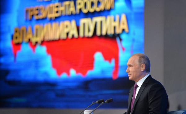 Russian President Vladimir Putin speaks in front of the map of the Russian Federation, with Crimea on the left of the map, during his annual news conference in Moscow, Russia, on Thursday. The Kremlin has responded angrily to the latest round of U.S.-EU s