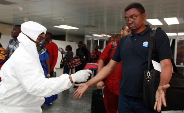 A health official uses a thermometer on a passenger at the international airport in Lagos, Nigeria.