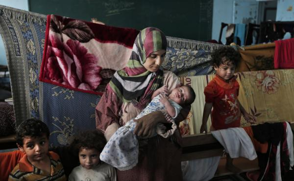 Displaced Palestinian Emada al-Attar, 23, holds her 16-day-old baby boy Anous on Aug. 8 in a classroom where they sleep in a United Nations school in Gaza City. Thousands of Palestinians lost their homes in the recent fighting and are still taking refuge