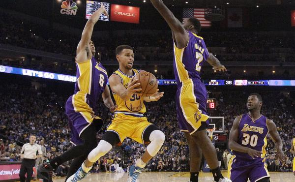 Golden State Warriors guard Stephen Curry, center, looks to pass as Los Angeles Lakers Jordan Clarkson (6), Brandon Bass (2) and Julius Randle (30) defend. The Warriors won, 111-77.