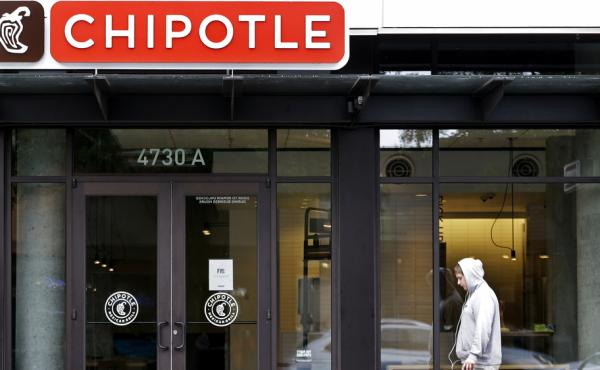 A passerby walks past a Chipotle restaurant in Seattle in November that closed following one of two E.coli outbreaks that sickened scores of people.
