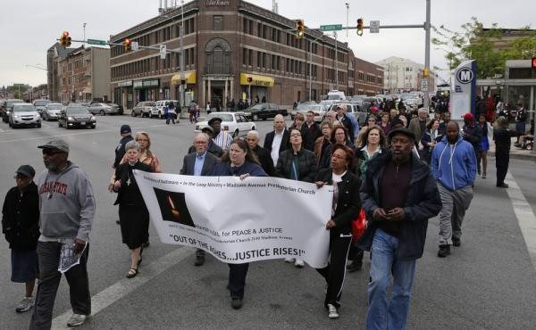 People march in the Penn North neighborhood of Baltimore on Wednesday, the anniversary of the funeral of Freddie Gray.