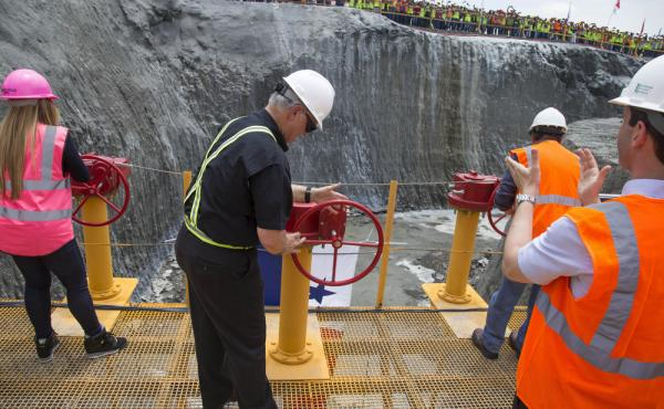 The head of the Panama Canal Authority, Jorge Quijano, center, opens the main valve to allow water into the flood chambers on the new set of locks on the Atlantic side of the Panama Canal in June 2015. The expansion of the canal, making it wider and deepe
