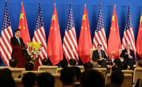 China's President Xi Jinping, left, speaks from the stage with U.S. Secretary of State John Kerry, right, and U.S. Treasury Secretary Jacob Lew, center, during the opening ceremony of the 8th U.S.-China Strategic and Economic Dialogues.
