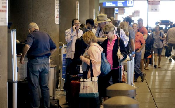 Passengers line up to check in before their flights in May at Sky Harbor International Airport in Phoenix. Two new automated security lanes at the Atlanta Airport are aimed at reducing long wait times.