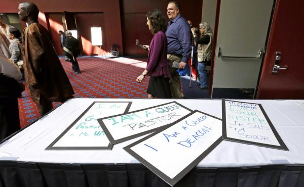 Attendees walk past a handful of placards during a break in the Methodists annual conference in Portland, Ore., in May 2016. The United Methodist Church, the nation's largest mainline Protestant denomination, was holding its once-every-four-years meeting