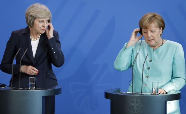 German Chancellor Angela Merkel (right), and British Prime Minister Theresa May (left), listen to translations during a joint news conference in Berlin on July 20. They are the two most important figures in the negotiations over Britain's departure from t