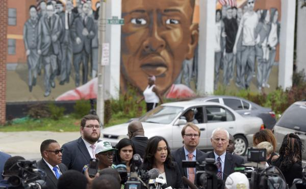 Baltimore State's Attorney Marilyn Mosby, center, speaks during a news conference Wednesday after her office dropped remaining charges against the three Baltimore police officers who were still awaiting trial in Freddie Gray' death. Third from left, in a